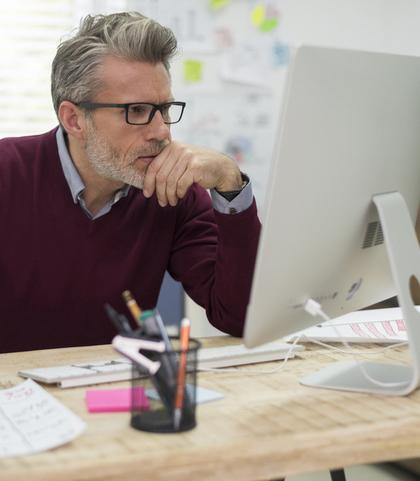 Mann mit Brille am PC